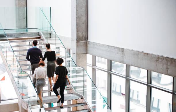 blick zurück auf die gruppe der jungen geschäftsleute, die die treppe hinauf gehen. - treppe stock-fotos und bilder