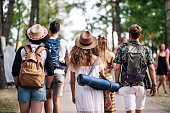 Rear view of group of young friends with backpack and mat walking at summer festival.