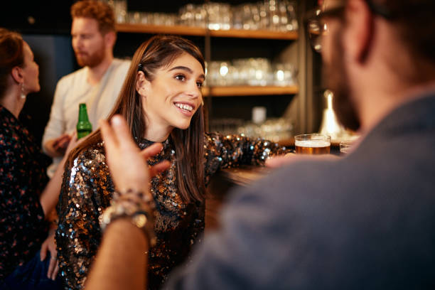 Rear view of handsome caucasian man leaning on bar counter, drinking beer and flirting with woman he just met. Pub interior. stock photo