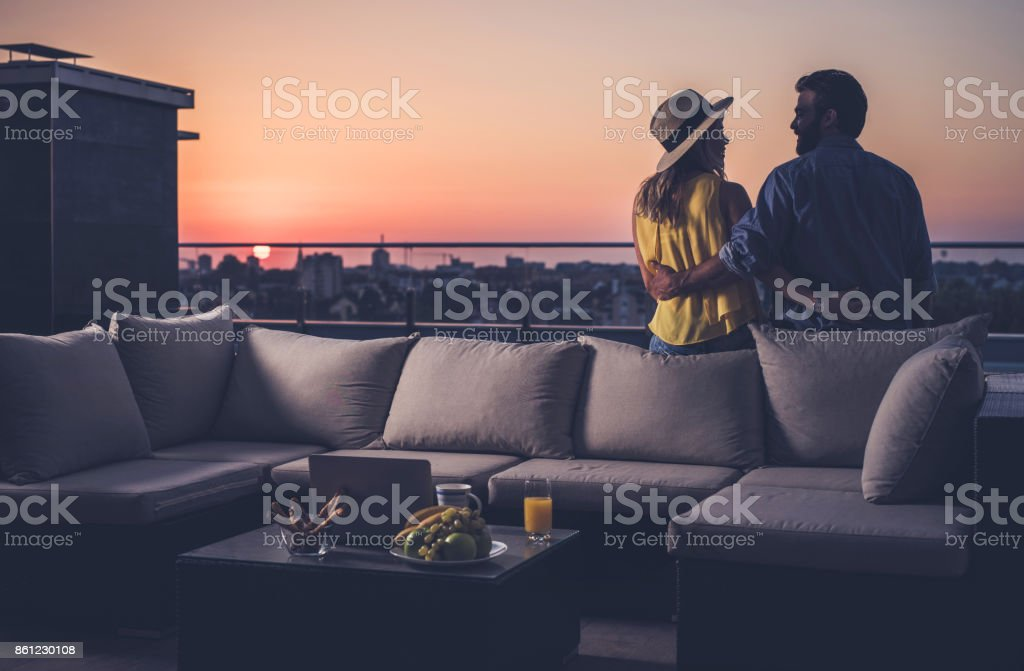 Rear view of happy couple communicating on a penthouse balcony at sunrise. stock photo