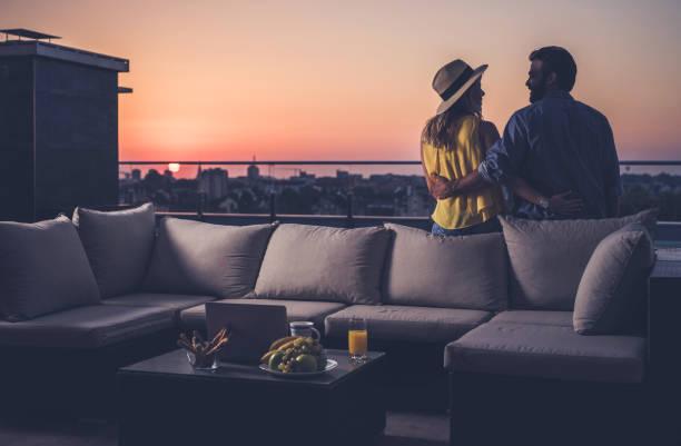 Vista traseira do casal feliz se comunicam em uma varanda de cobertura ao nascer do sol. - foto de acervo