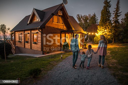Back view of young smiling parents holding hands with their children and walking in nature in the evening.
