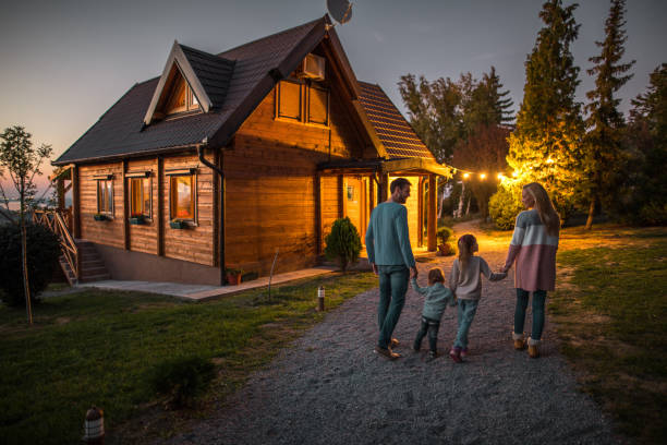 Rear view of happy family holding hands and walking by their chalet in the evening. Back view of young smiling parents holding hands with their children and walking in nature in the evening. chalet stock pictures, royalty-free photos & images