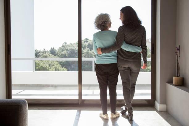 Rückansicht glücklicher Mutter und Tochter, die umarmt – Foto