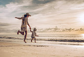 Back view of carefree mother and son holding hands while jumping on the beach at sunset. Copy space.