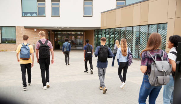 rear view of high school students walking into college building together - school building stock photos and pictures