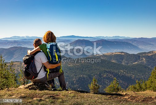 Rear view of hikers couple with backpack sitting on top of the mountain and enjoying the view during the day.