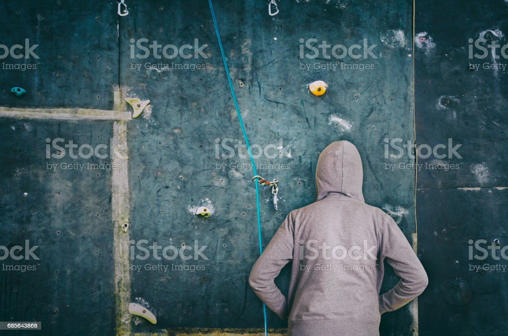 Rear view of hooded man against artificial rock climbing wall royalty-free 스톡 사진