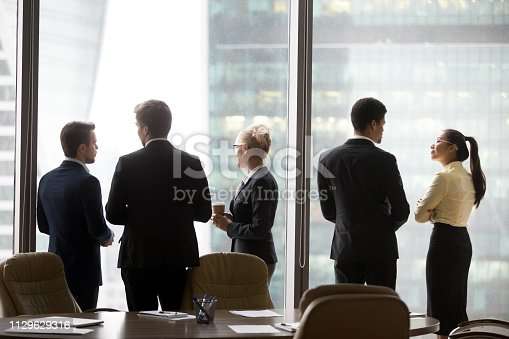 istock Rear view of international executives team talking near office window 1129629316