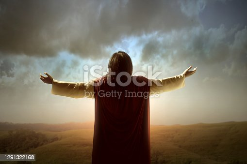 istock Rear view of Jesus Christ raised hands and praying to god 1291322168