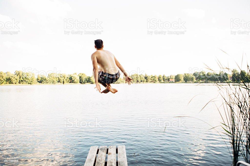 Rückansicht des jungen Springen vom Bootssteg an einem See – Foto