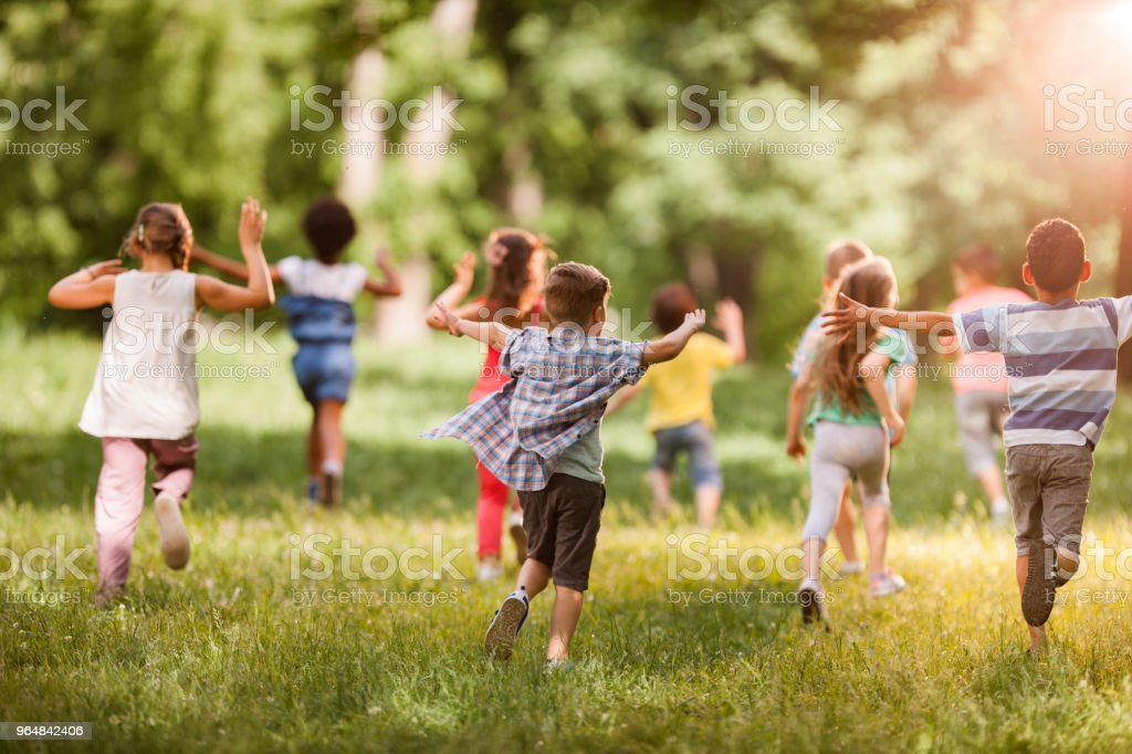 Rear view of large group of children running in springtime. stock photo