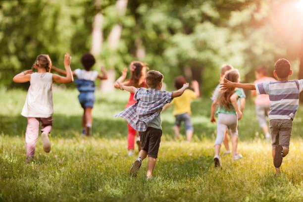 春に動いている子供の大規模なグループの後姿。 ストックフォト