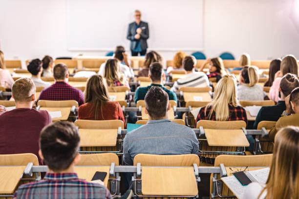 opinião traseira o grande grupo de estudantes em uma classe no salão de leitura. - universidade - fotografias e filmes do acervo