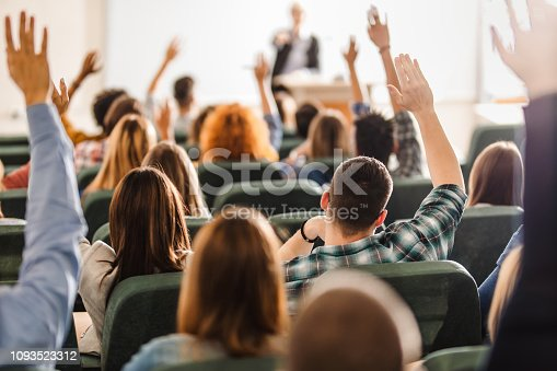 Back view of college students raising their arms on a class at lecture hall.