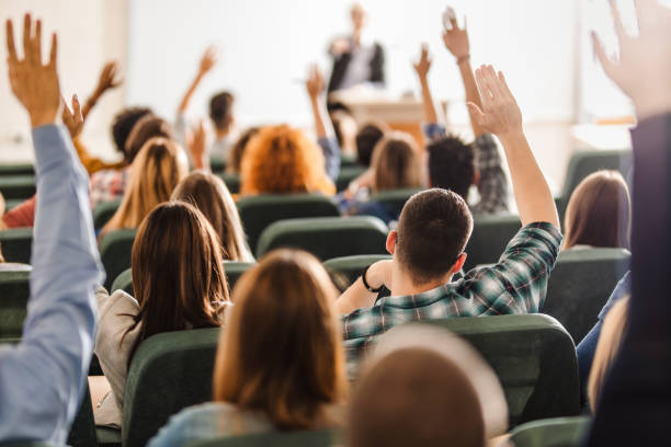 rear view of large group of students raising arms during a class at amphitheater. - classrooms stock pictures, royalty-free photos & images