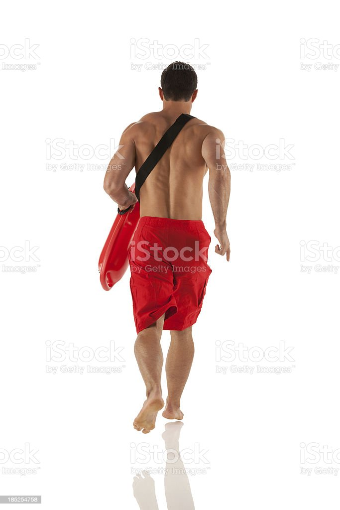 Rear view of lifeguard carrying a float royalty-free stock photo