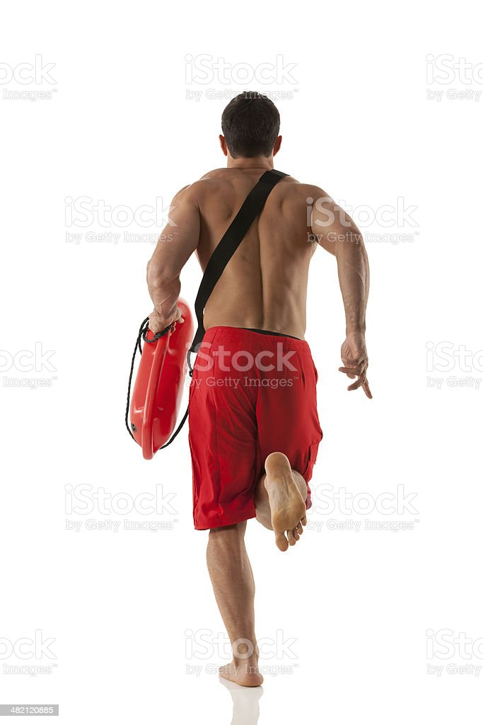 Rear view of lifeguard running with float royalty-free stock photo
