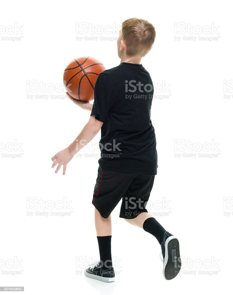 Rear view of little boy playing basketball stock photo