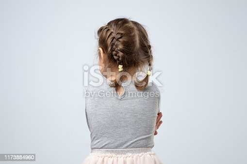 Rear view of little caucasian girl. Kid is lost or being offended on her parents. Studio shot