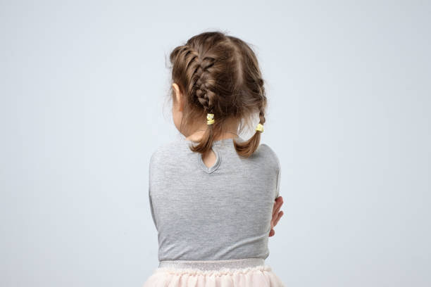 Rear view of little caucasian girl. Kid is lost or being offended on parents. stock photo
