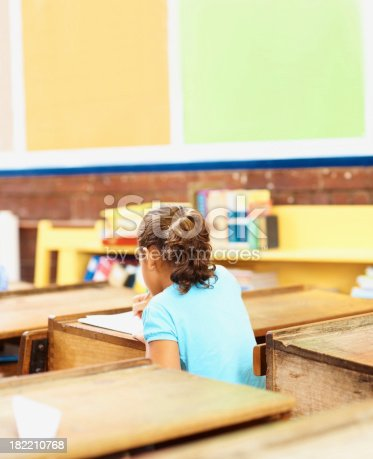 istock Rear view of little school girl at her desk 182210768