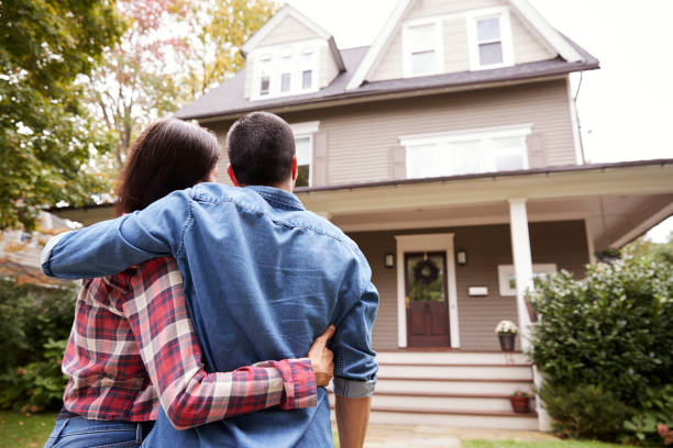 rear view of loving couple looking at house - home ownership stock photos and pictures