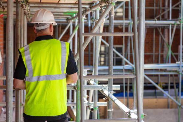 Vista trasera del contratista trabajador de la construcción del constructor masculino en el sitio de construcción con sombrero duro y chaleco amarillo de alta visibilidad - foto de stock