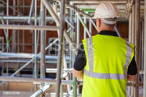 Rear view of male builder construction worker on building site wearing hard hat and hi-vis vest