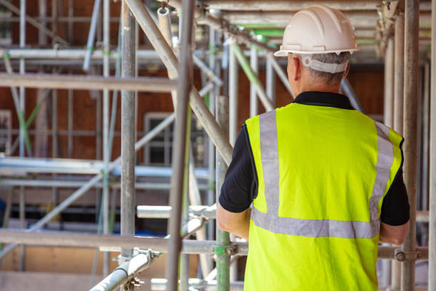 Rear view of male builder construction worker on building site wearing hard hat and hi-vis vest Rear view of male builder construction worker on building site wearing hard hat and hi-vis vest scaffolding stock pictures, royalty-free photos & images