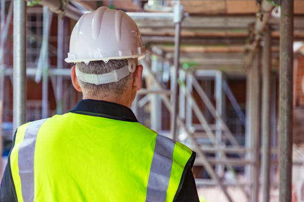 Rear view of male builder construction worker on building site wearing hard hat and hi vis vest Rear view of male builder construction worker on building site wearing a white hard hat and hi vis vest scaffolding stock pictures, royalty-free photos & images