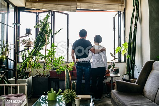 Couple standing and looking at view from apartment, mature man and senior woman, affection, love, togetherness