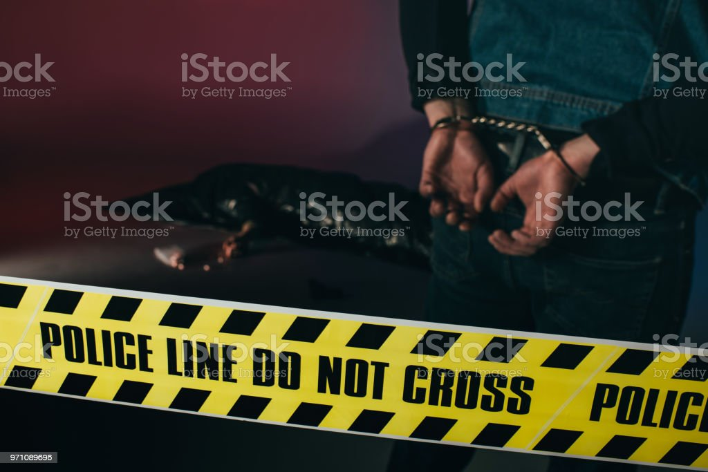 Rear view of man in cuffs by dead body behind yellow tape on dark background stock photo