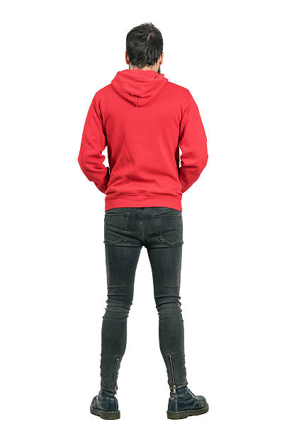 Rear view of man in jeans and boots wearing hoodie Rear view of young man in tight jeans and boots wearing red hoodie. Full body length portrait isolated over white studio background. men in tight jeans stock pictures, royalty-free photos & images