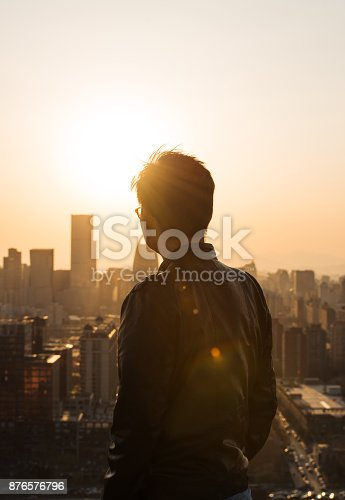istock Rear view of Man looking at city in Sunlight 876576796