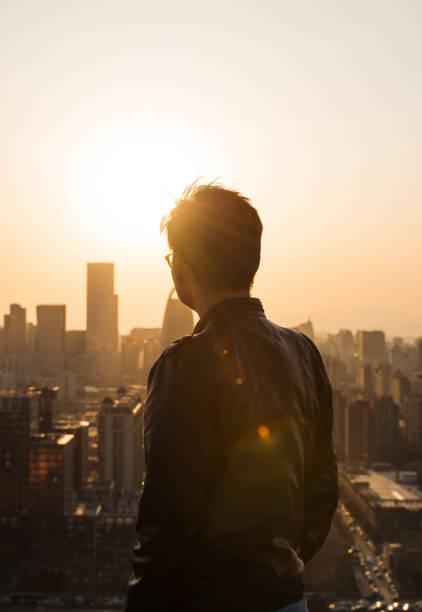 rückansicht des menschen blick auf stadt im sonnenlicht - gegenlicht stock-fotos und bilder