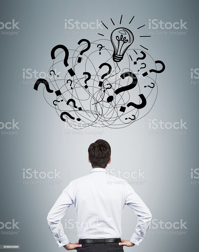 Rear view of man looking at question marks stock photo