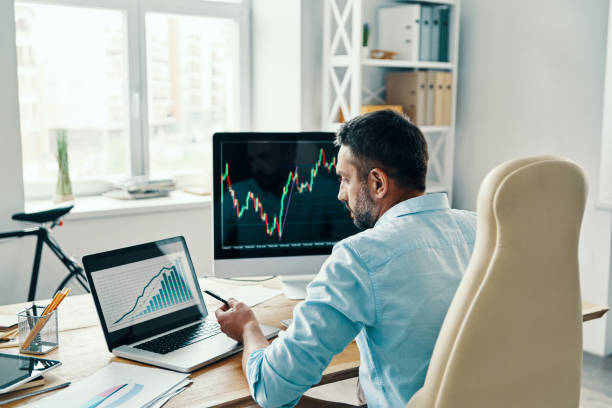 Rear view of man Rear view of man in smart casual wear analyzing stock market data while sitting in the office investor stock pictures, royalty-free photos & images
