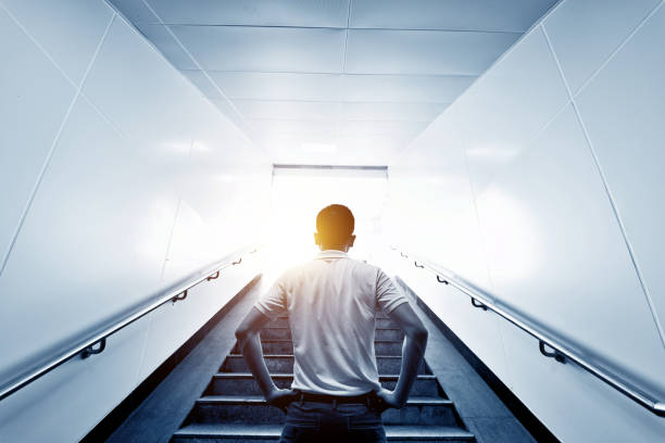 Rear view of man standing at the staircases Rear view of man standing at the staircases. akimbo stock pictures, royalty-free photos & images