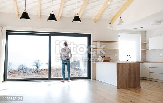 istock Rear view of man standing in unfurnished house, moving in new home concept. 1199612124