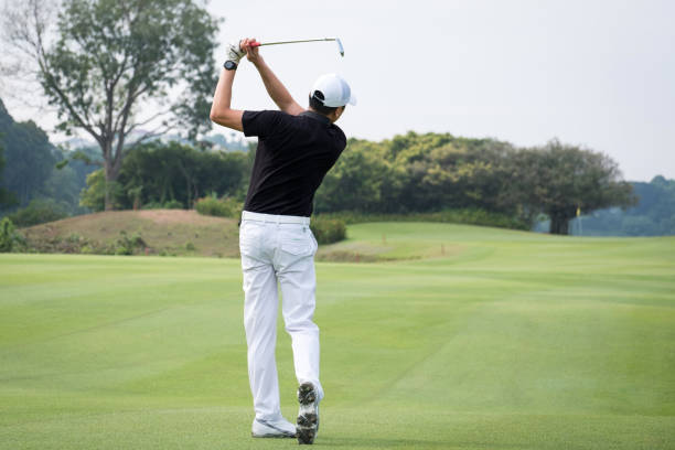Rear view of man teeing off on golf course stock photo