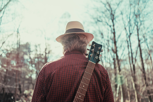 Color image depicting the rear view of a man wearing a red check shirt, denim jeans and a straw hat while walking on a beautiful tree lined country road. He is enjoying the freedom of exploring and wandering in nature, and he has an acoustic guitar strapped to his back. Room for copy space.