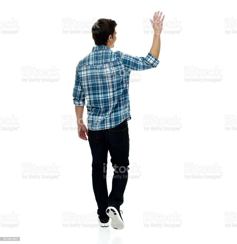 Rear view of man waving hand and walking stock photo