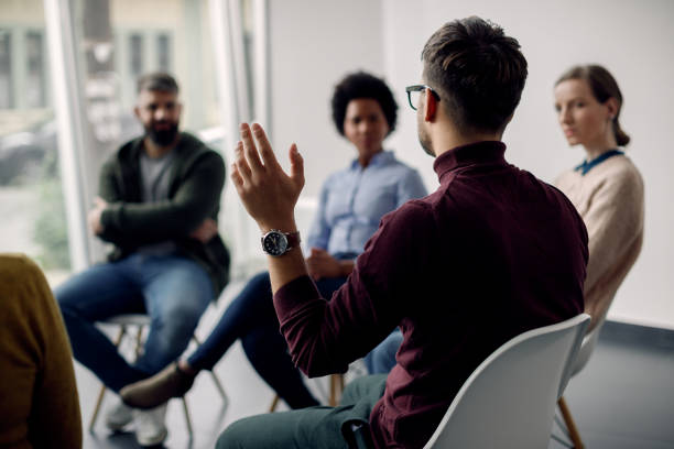 Rear view of man with raised hand on group therapy in medical center. stock photo