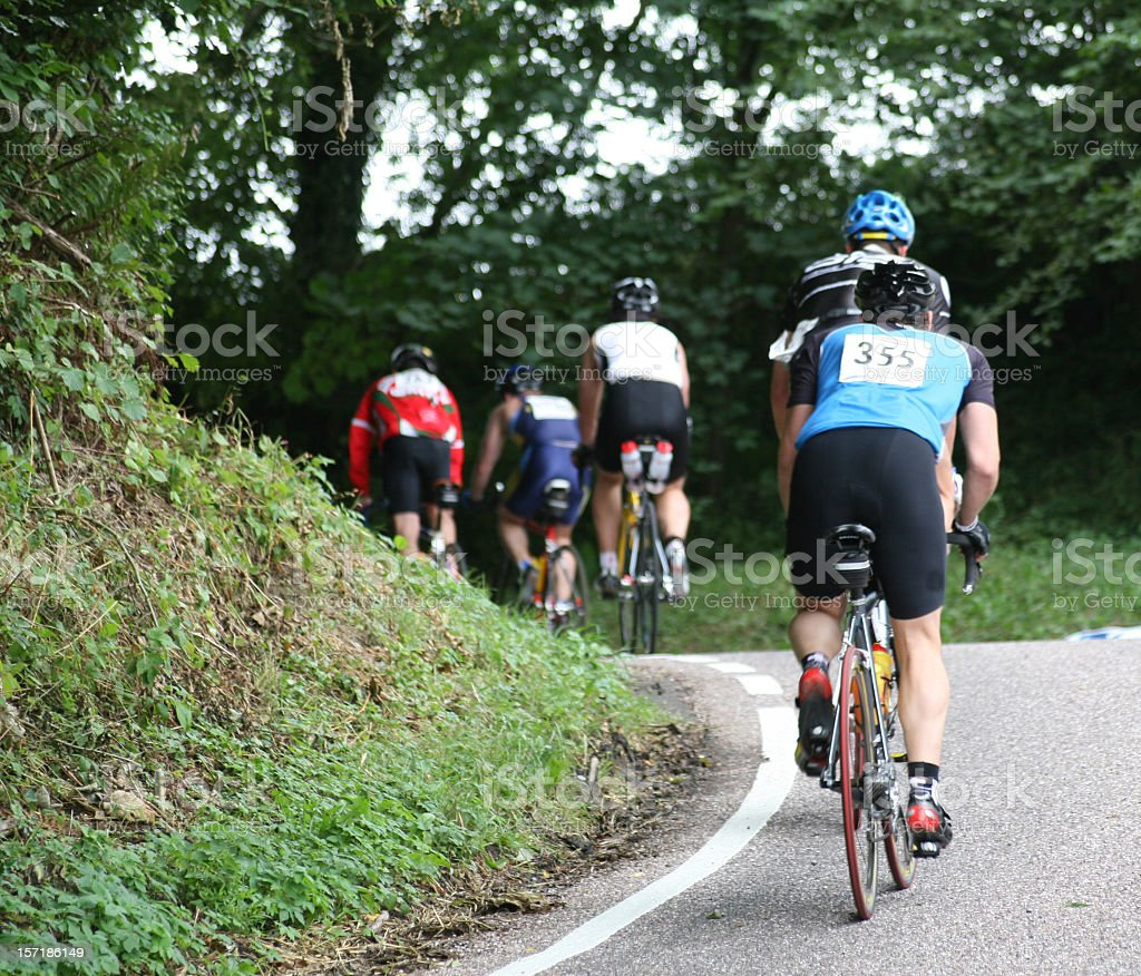 Rear view of many cyclists on a road during a bike race royalty-free stock photo
