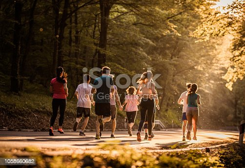 Back view of group of people running a marathon on asphalt road at sunset.
