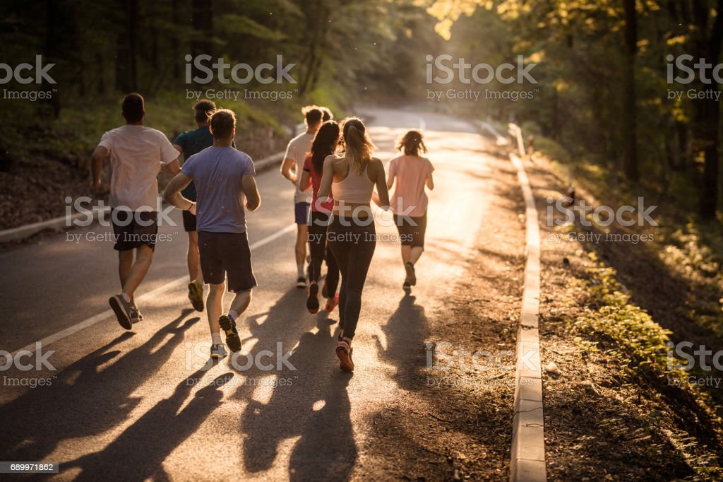 Rear view of marathon runners racing at sunset.