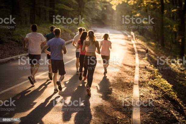 Rear view of marathon runners racing at sunset picture id689971862?b=1&k=6&m=689971862&s=612x612&h=vlgmpf62izab8sssktnwhuq0z sgauaqg55agozznqu=