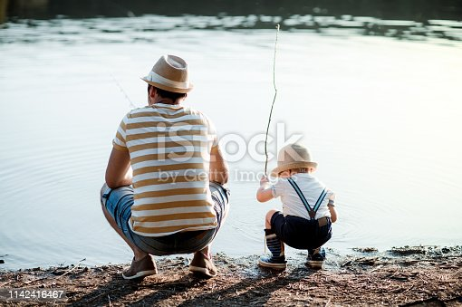 A rear view of mature father with a small toddler son outdoors fishing by a river or a lake.