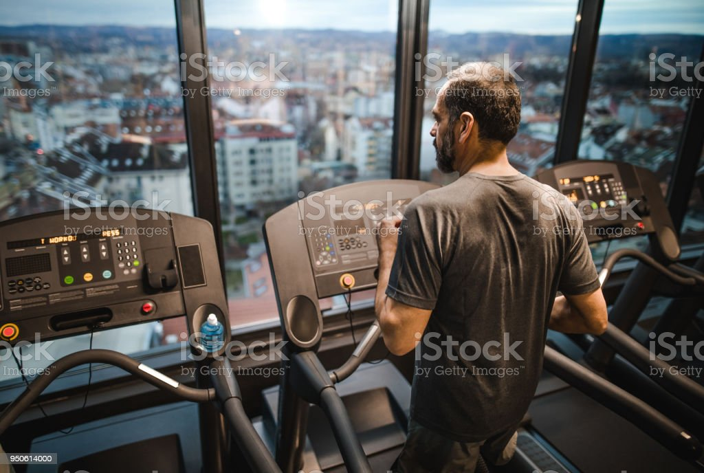 Rear view of mature man jogging on treadmill in a gym. stock photo